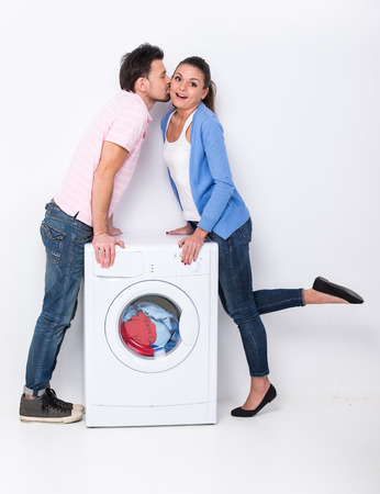 Young man is kissing woman near the washing machine at home.