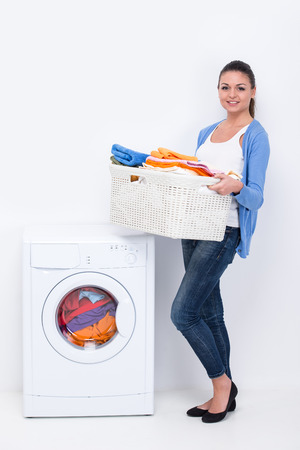 Young housewife is doing laundry with washing machine at home.