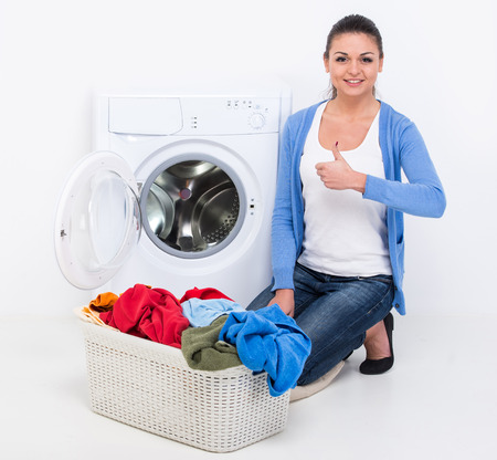 Happy young woman is doing laundry with washing machine at home.