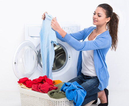 work clothes: Happy young woman is doing laundry with washing machine at home.
