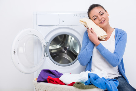dirty girl: Young housewife is doing laundry with washing machine at home.