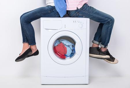 젊은 부부는 흰색 배경에 세탁기에 앉아있다.