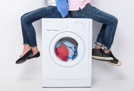 chore: Young couple are sitting on the washing machine, on the white background. Stock Photo
