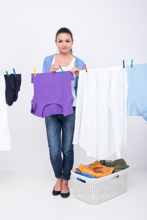 Young woman is hanging clothing on clothesline on white . photo