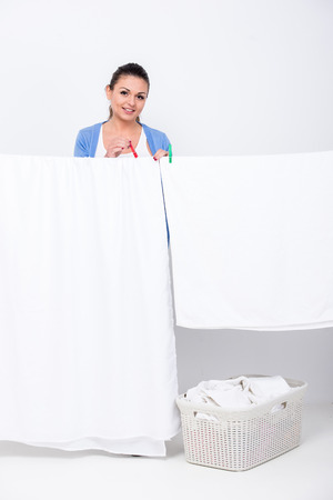 bedclothes: Young woman is hanging bedclothes on clothesline on white .