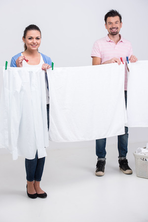 bedclothes: Young couple are hanging bedclothes on clothesline on white .
