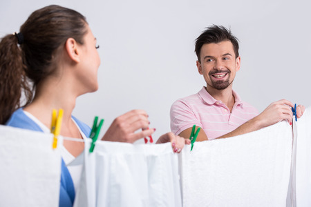 bedclothes: Young smiling couple are hanging bedclothes on clothesline on white .