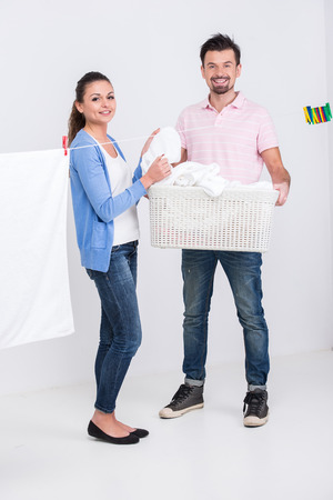Young happy couple are hanging bedclothes on clothesline on white . photo