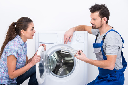 Repairman is repairing a washing machine for housewife.