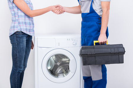 Apretón de manos de ama de casa y reparador cerca de la lavadora.