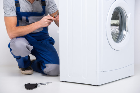 home appliances: Repairman is repairing a washing machine on the white background. Stock Photo