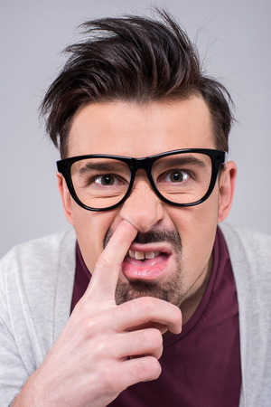 spectacled: Young spectacled man and his finger in the nose. The human face, expression, emotion, body language. Stock Photo