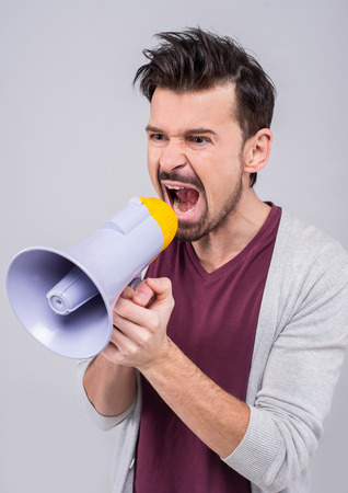 making an announcement: Young man is making announcement over a megaphone on the gray background.