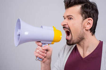 making an announcement: Side view of young man is making announcement over a megaphone on the gray background. Stock Photo