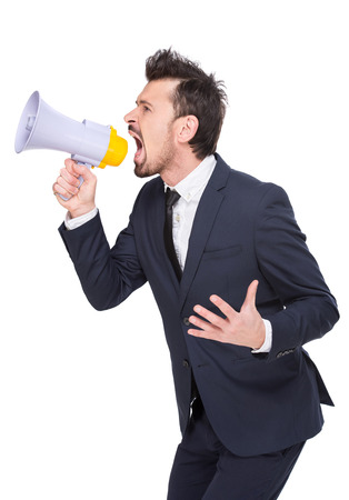 making an announcement: Side view of young man is making announcement over a megaphone on the white . Stock Photo