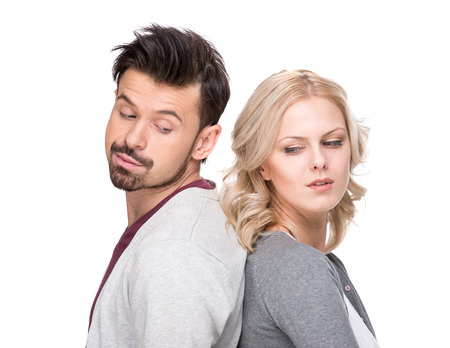 personas de espalda: Hombre joven infeliz y mujer están de pie de nuevo entre sí y no habla, aisladas sobre fondo blanco.