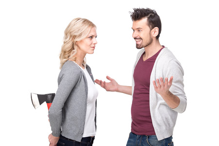 Deception. Conflict. Young couple, man is smiling and woman holding ax behind. White background. Stock Photo
