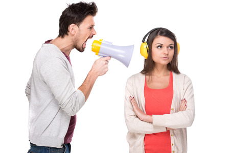 Young man shouts at the woman in a megaphone. Woman with headphones while he screams.  스톡 콘텐츠