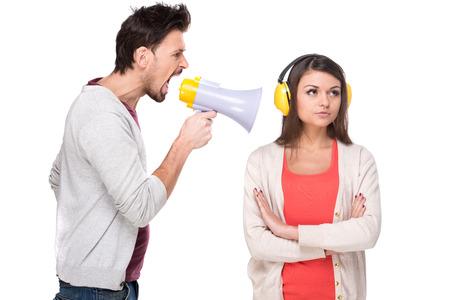 pareja enojada: Hombre joven que grita a la mujer en un megáfono. Mujer con los auriculares mientras grita.