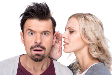 Amazed man is listening gossip in the ear from woman, on the white background.