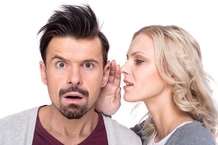 Verbaasd man luistert roddels in het oor van de vrouw, op de witte achtergrond.