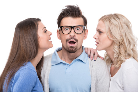 Emotional young man with glasses and two beautiful women on white background. photo
