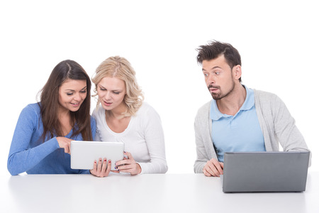 Two young women are looking at tablet. Man with laptop is spying. photo