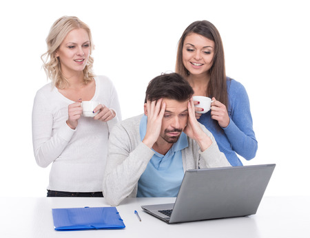 Tired man with laptop on the table and young smiling women with a cup of coffee. photo