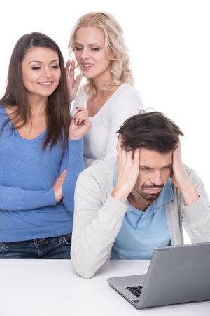 Tired man with laptop on the table and young smiling women are gossip behind him. photo