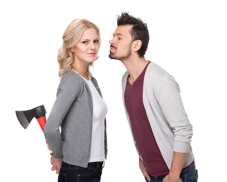 Deception. Conflict. Young couple, man wants to kiss his girlfriend and she is holding ax behind. White background. photo