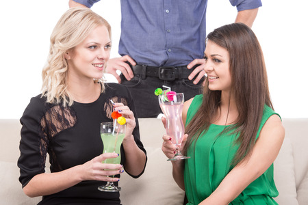 Two young women with cocktails on the couch, the man is standing behind them. photo