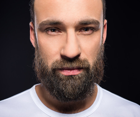 Portrait of a young brutal man with full beard. Black background.