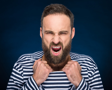 striped vest: Portrait of a young brutal man with full beard in striped vest.  Stock Photo