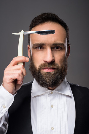 brutal: Portrait of a young brutal bearded man with straight razor. Grey background. Stock Photo