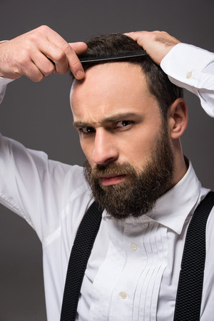 straight man: Portrait of a young brutal bearded man with straight razor. Grey background. Stock Photo
