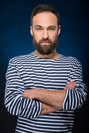 Portrait of a young brutal man with full beard in striped vest.