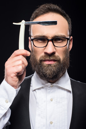 brutal: Portrait of a young brutal bearded man with straight razor.