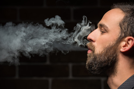 Side view of young bearded man is smoking against brick wall.