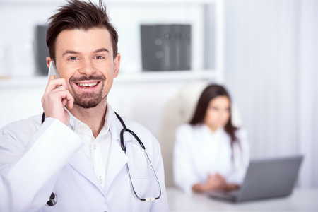 Smiling male doctor is looking at the camera while speaking by phone. Assistant sits at the table with laptop. photo