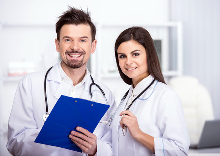 Two smiling doctors are looking at the camera in medical room. photo