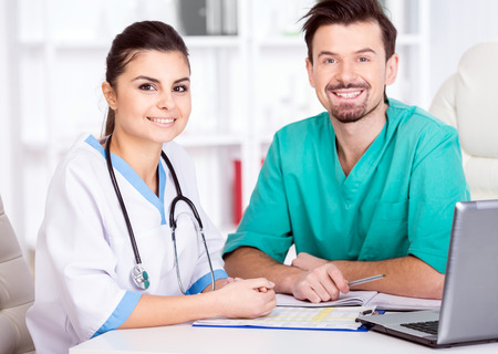 The young doctor and his assistant in a medical office at work. photo