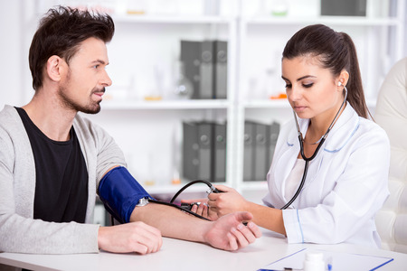 Beautiful young female doctor is checking the blood pressure of the patient. Standard-Bild