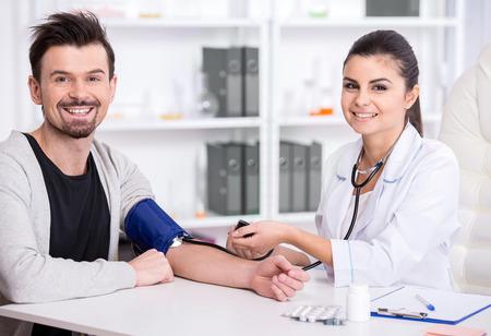 美しい若い女性医師は、患者の血圧をチェックします。