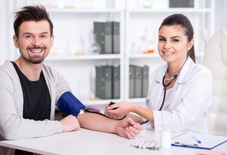 Beautiful young female doctor is checking the blood pressure of the patient. Фото со стока
