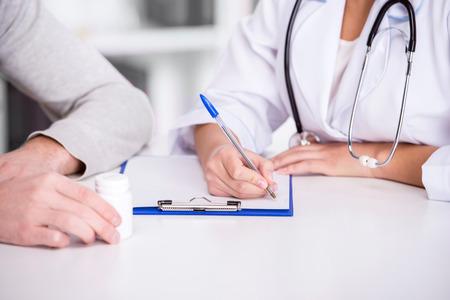 Gezondheidszorg en geneeskunde concept. Jonge mannelijke arts met klembord en patiënt in het ziekenhuis.