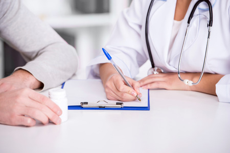 consulta m�dica: Salud y concepto de la medicina. Doctor de sexo masculino joven con el sujetapapeles y el paciente en el hospital. Foto de archivo