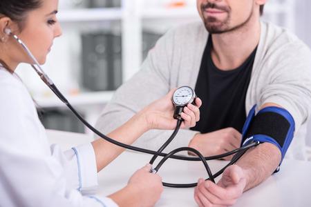 Piękna młoda kobieta lekarz jest sprawdzanie ciśnienie krwi pacjenta. Zdjęcie Seryjne