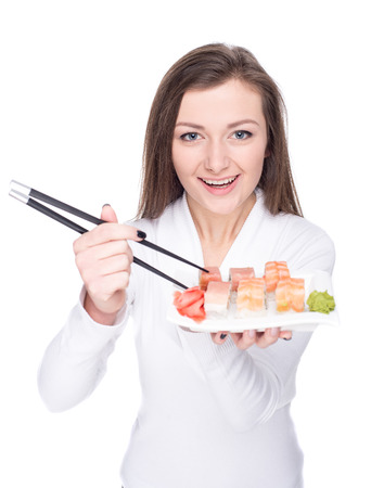 Beautiful young woman is holding a plate with sushi, isolated against white background. Stock Photo