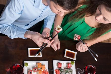 pareja comiendo: Pareja joven est� comiendo sushi en el restaurante. Vista superior. Foto de archivo