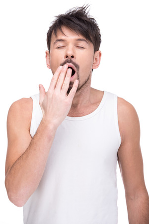 mimic: Sleepy young man is yawning on the white background.